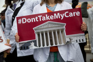 Demonstrator Nell Robinson, a medical student from George Washington University, holds a sign in favor of to U.S. President Barack Obama's health-care law, Obamacare, in front of the U.S. Supreme Court in Washington, D.C., U.S., on Wednesday, March 4, 2015.