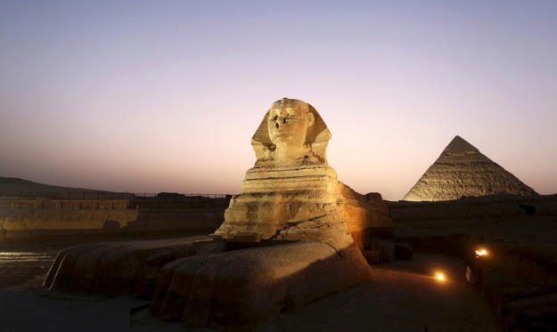 The sphinx (C) is pictured near the pyramids of Menkaure (R) and Khafre in Giza, during its reopening ceremony November 9, 2014. The Great Sphinx of Giza, which sits next to the ancient Pyramids, reopens after undergoing major restoration work, including repairs to its worn out base, in a ceremony attended by the country's top officials, including Prime Minister Ibrahim Mahlab. REUTERS/Mohamed Abd El Ghany (EGYPT - Tags: SOCIETY TRAVEL)