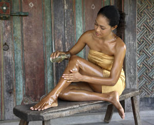 A woman applying coconut oil on her body.