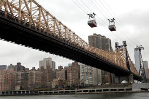 The Roosevelt Island trams are framed by the Queensboro Bridge and the Manhattan skyline as they make their way over the East River into Roosevelt Island.