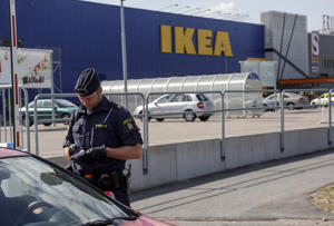 A police office talks to customers outside the Ikea store in Vasteras, Sweden, Monday Aug. 10, 2015, after three people were injured in a knife attack at the store.