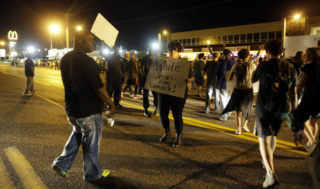 Crowds chant in the street along West Florissant Avenue, Monday, Aug. 10, 2015, in Ferguson, Mo. Ferguson was a community on edge again Monday, a day after a protest marking the anniversary of Michael Brown's death was punctuated with gunshots.