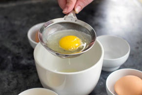 This July 28, 2014 photo shows an egg in a strainer in Concord, N.H. The thinner...