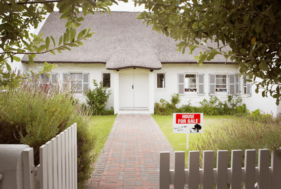 Slide 1 of 10: House with for sale sign in yard and open wooden fence