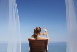 A woman sitting on a lounge chair and applying sunscreen.