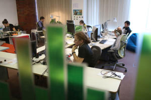 Employees work at their desks at the headquarters of an internet company.