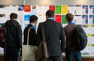Visitors look at employment opportunities displayed on a job board at the Connecticum job fair in Berlin, Germany.