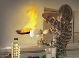 Woman shielding face from kitchen frying pan fire. Andrew Bret Wallis/Getty Imag...