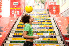 Model Released - Young woman doing keepy uppys in front of the Escadaria Selaron steps in Rio de Janiero, Brazil