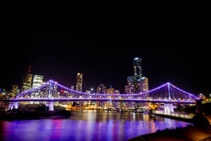 The Story Bridge stands illuminated at night over the Brisbane River in front of buildings in Brisbane, Australia.