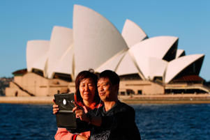 Tourists pose for a selfie at the Sydney Opera House in Sydney, Australia.