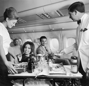 circa 1965: Flight crew serving food and beverages to passengers aboard an airplane, 1960s. (Photo by R. Gates/Hulton Archive/Getty Images)