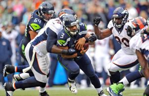 Denver Broncos defensive tackle Malik Jackson, left, and defensive end Antonio Smith, right, bring down Seattle Seahawks quarterback Russell Wilson during the first half in a preseason NFL game at CenturyLink Field on Aug. 14 in Seattle.