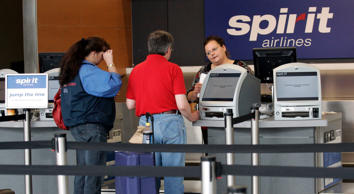 Two passengers talk to a ticketing agent at the Spirit Airlines counter.