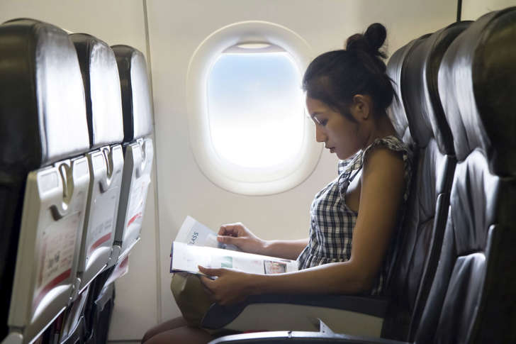 Woman reading a magazine during a flight.