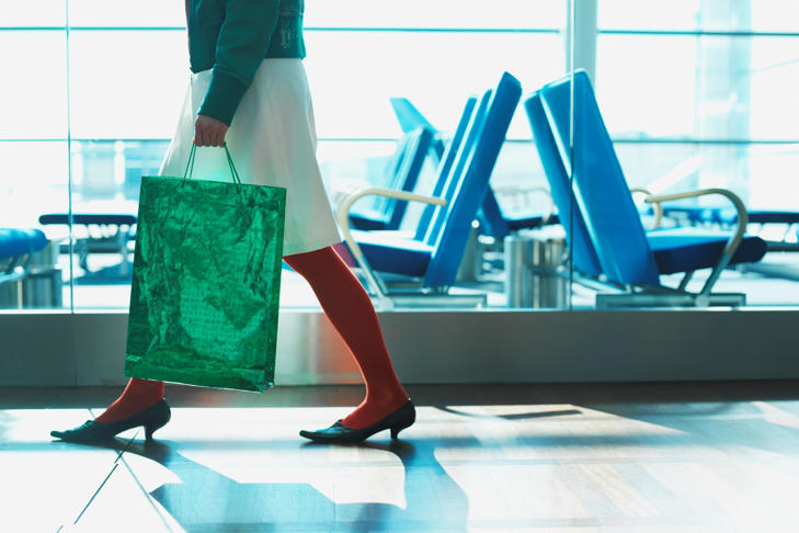Woman carrying shopping bag in an airport.