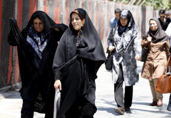 Women walk on a sidewalk in northern Tehran, Iran, on July 27.