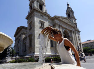 A woman dips her head into a fountain in Budapest, Hungary July 6, 2015. Over the weekend, a heat wave has reached Hungary with temperatures topping 38 degrees Celsius (100.4 degrees Fahrenheit).