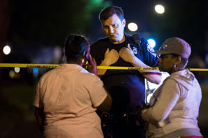A police officer speaks to bystanders at the scene of a drive-by shooting at the Boys and Girls Club on Genesee Street, early Thursday, Aug. 20, 2015, in Rochester, N.Y. The gunman shot into a crowd that gathered outside the club after a basketball game, fatally wounding several people.