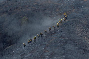 A hot shot crew descends a scorched mountainside at the Cabin Fire in the Angeles National Forest on August 15, 2015 north of Azusa, California. The fire has grown to 2,500 acres with 0% containment under heat wave conditions.