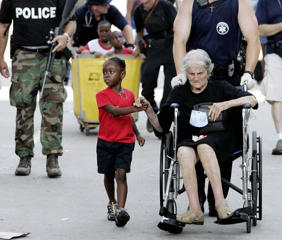 Tanisha Belvin, 5, holds the hand of fellow Hurricane Katrina victim Nita LaGarde, 89, as they are evacuated from the  Convention Center in New Orleans, La., Saturday, Sept. 3, 2005.  Hundreds of people waited several days to be evacuated.  (AP Photo/Eric Gay)