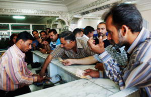 An Iraqi travel agent checks passports of Iraqis wanting to travel outside Iraq  in Baghdad, Iraq.