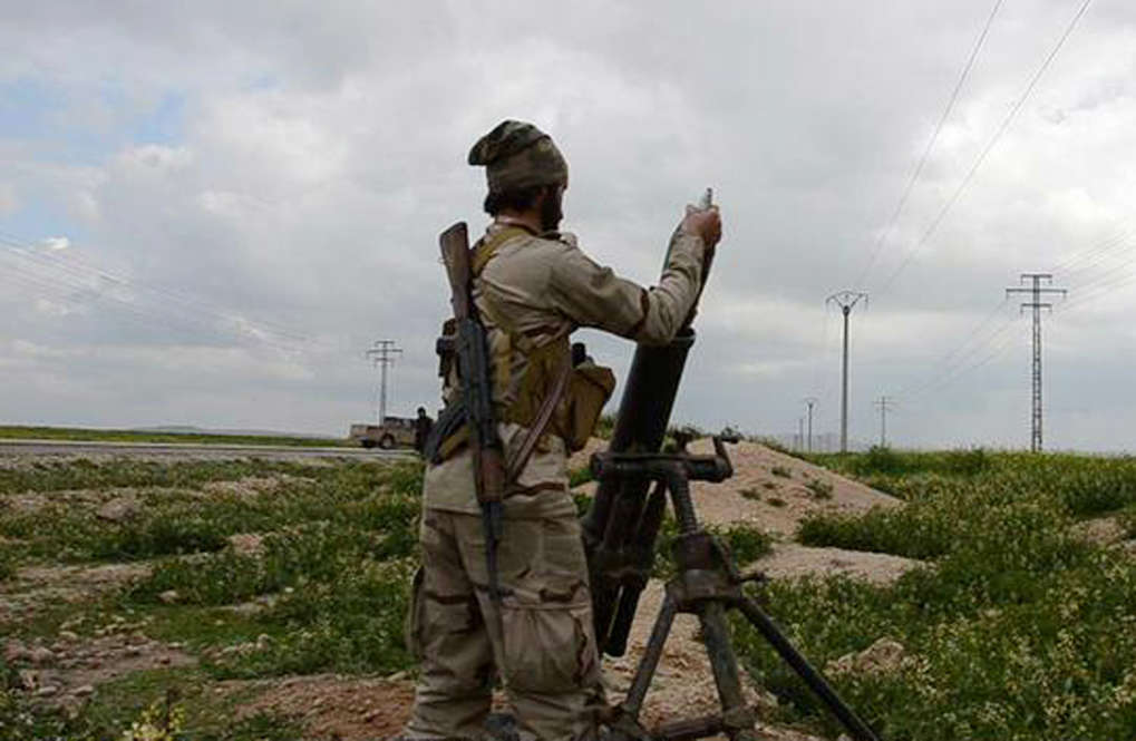 In this photo released on March 23, 2015, by a militant website, which has been verified and is consistent with other AP reporting, an Islamic State militant fires a mortar against Kurdish fighters, at the frontline near Tel Abyad town, northeast Syria.