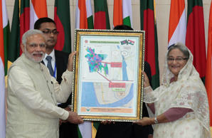 File: Bangladesh's Prime Minister Sheikh Hasina, right, and Indian Prime Minister Narendra Modi hold a location map of Indian Economic Zones during an agreement program in Dhaka, Bangladesh, Saturday, June 6, 2015. Relations between India and its smaller neighbor have significantly improved since Hasina promised that her administration would not allow India's separatist insurgents to use the porous 4,000-kilometer (2,500-mile) border to carry out raids in India.