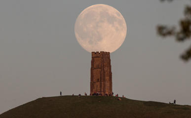 The moon rises over people gathered on Glastonbury Tor ahead of tomorrow's Blue Moon on July 30, 2015 in Somerset, England.