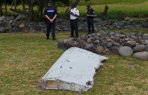 French police stand near a large piece of plane debris  found on the French Indian Ocean island of La Reunion.