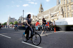 Comedian Russell Brand cycles away from Parliament Square on a hired 'Boris Bike'  in London.