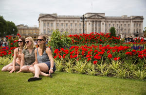 Tourists pose as a friend photographs them in front of Buckingham Palace.