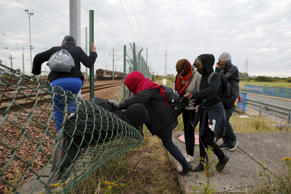 Migrants make their way across a fence near near train tracks as they attempt to access the Channel Tunnel in Frethun, near Calais, France, July 29, 2015. A migrant died trying to cross to Britain from France early on Wednesday, French police said, adding to a number of recent deaths in the Channel Tunnel as British ministers and security chiefs were to meet over the crisis in Calais. There were about 1,500 attempts by migrants to access the tunnel on Tuesday night, a Eurotunnel spokesman said, after 2,000 attempts the previous night. REUTERS/Pascal Rossignol TPX IMAGES OF THE DAY