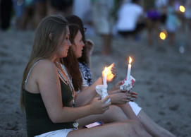 Julia Wolf, 16, left, and Jordan Harley, right, both of Stuart, Fla., hold candles during a vigil for Austin Stephanos and Perry Cohen, on Tuesday in Stuart, Fla.