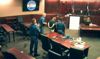 In this image made from Colorado Judicial Department video, Deborah Cave, center, in handcuffs and in the custody of sheriff's deputies, appears before Judge Carlos A. Samour Jr., top second from right, who sentenced her to three weeks in jail for contempt of court for earlier climbing over seats and shouting during the closing argument of the prosecution in the James Holmes trial's sentencing phase in Centennial, Colo., Thursday, July 30, 2015.