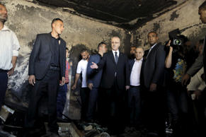 Palestinian Prime Minister Rami Hamdallah (center) inspects a house that was set on fire in a suspected attack by Jewish extremists in Duma village near the West Bank city of Nablus July 31, 2015.