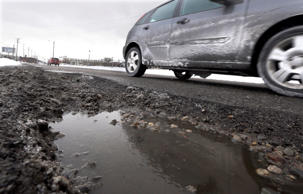 A vehicle passes a pothole on Oakland Avenue in Highland Park, Mich.