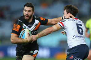 James Tedesco of the Wests Tigers fends off James Maloney of the Roosters during the round 20 NRL match on July 24, 2015 in Sydney, Australia.