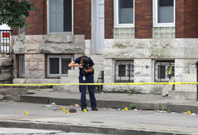 An investigator photographs the scene of a shooting, Monday, July 27, 2015, in Baltimore. Police said a male was shot in the chest near the epicenter of unrest in April following the funeral of Freddie Gray. Rioting and looting broke out in the area after the funeral of Gray, a black man who suffered a fatal spinal cord injury in police custody.