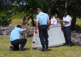 French gendarmes and police inspect a large piece of plane debris which was found on the beach in Saint-Andre, on the French Indian Ocean island of La Reunion, July 29, 2015. France's BEA air crash investigation agency said it was examining the debris, in coordination with Malaysian and Australian authorities, to determine whether it came from Malaysia Airlines Flight MH370, which vanished last year in one of the biggest mysteries in aviation history