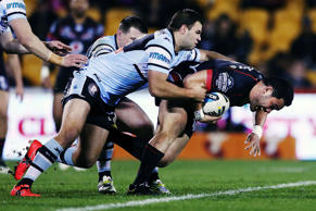 Konrad Hurrell of the Warriors charges on against Wade Graham of the Sharks.