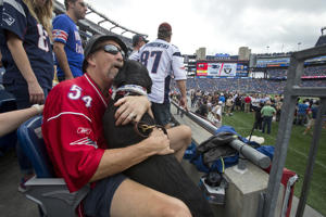 Randy Pierce, a blind season ticket holder, gets a pregame hug from his guide dog Autumn in his seats at Gillette Stadium. (Photo by Stan Grossfeld/The Boston Globe via Getty Images)