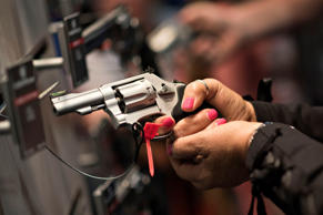 Attendees look over hand guns in the Smith & Wesson booth on the exhibition floor of the 144th National Rifle Association. Daniel Acker/Bloomberg