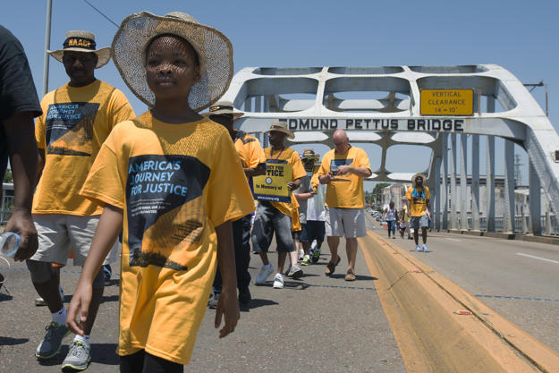 "Velivia Peterson, 8, walks with others across the Edmund Pettus Bridge during the start of the ""America's Journey for Justice March"" organized by the NAACP on Saturday, Aug. 1, 2015, in Selma, Ala. The 860 mile relay march is planned to go from Selma to Washington D.C. over the course of 40 days."
