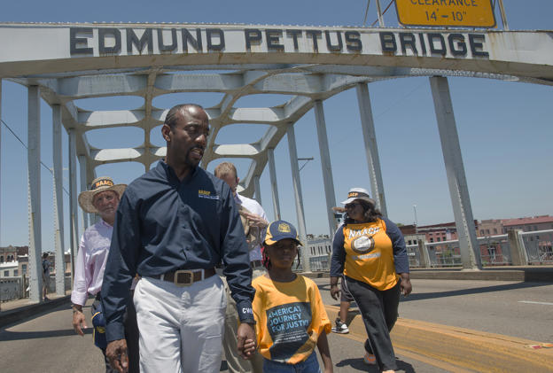 "Cornell William Brooks, NAACP president, holds the hand of Rachel Quarterman, 7, while leading the ""America's Journey for Justice March"" organized by the NAACP on Saturday, Aug. 1, 2015, in Selma, Ala."