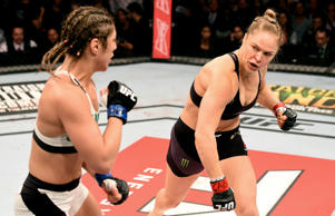 Ronda Rousey of the United States throws a punch at Bethe Correia of Brazil in their UFC women's bantamweight championship bout during the UFC 190 event inside HSBC Arena on August 1, 2015 in Rio de Janeiro, Brazil.