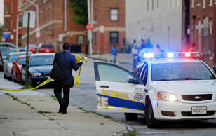 A member of the Baltimore Police Department removes crime scene tape from a corner where a victim of a shooting was discovered in Baltimore. Murders are spiking again in Baltimore, three months after Freddie Gray's death in police custody sparked riots.
