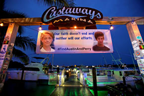 A banner hangs at the Castaways Marina with pictures of Austin Stephanos and Perry Cohen. After 8 days of searching the ocean, the U.S. Coast Guard ended their search for the boys. Friends and relatives attended a fundraiser at the Square Grouper, Friday, July 31, 2015 in Jupiter, Fla.