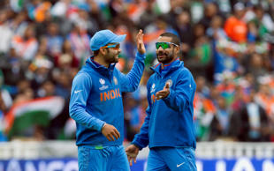 India's Virat Kohli, left, celebrates with teammate Shikhar Dhawan after running out Pakistan's Junaid Khan for 0 during their ICC Champions Trophy cricket match at Edgbaston cricket ground, Birmingham, England, Saturday June 15, 2013.