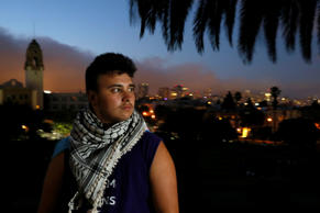 Alex Bergeron, 20, wears his Muslim father's kaffiyeh scarf during an evening on July 15, 2015 in San Francisco's Mission Dolores Park. Alex finds it difficult to pray in a mosque now that he has changed his gender from female to male.